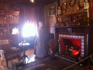 One of the rooms in Eldon House, with a fire place, a manequin dressed as a maid and many decorations on the wall.